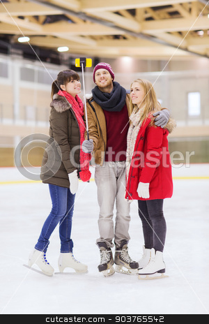 happy friends taking selfie on skating rink stock photo, people, friendship, technology and leisure concept - happy friends taking picture with smartphone and selfie stick on skating rink by Syda Productions
