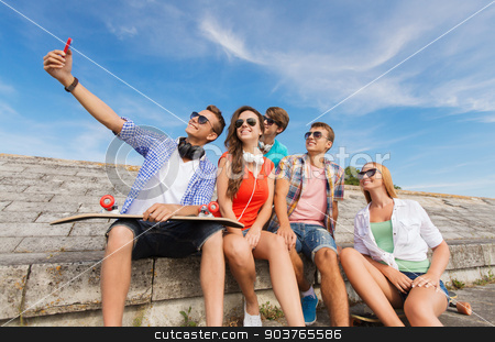 group of smiling friends with smartphone outdoors stock photo, friendship, leisure, summer, technology and people concept - group of smiling friends with skateboard and smartphone making selfie outdoors by Syda Productions