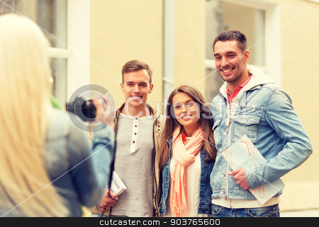 group of smiling friends taking photo outdoors stock photo, travel, vacation, technology and friendship concept - girl picturing group of friends with map and city guide in city by Syda Productions