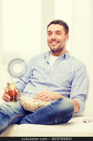 smiling man with beer and popcorn at home stock photo, home, technology and entretainment concept - smiling man with beer and popcorn at home by Syda Productions