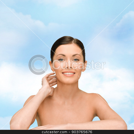 smiling young woman with bare shoulders stock photo, beauty, people and health concept - smiling young woman with bare shoulders over blue sky background by Syda Productions