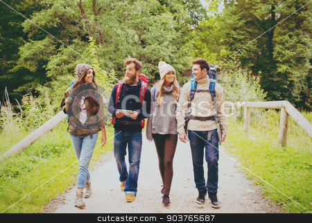 group of friends with backpacks and tablet pc stock photo, adventure, travel, tourism, hike and people concept - group of smiling friends with backpacks and tablet pc computer walking outdoors by Syda Productions
