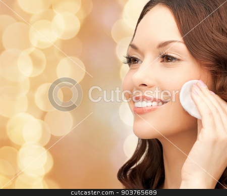 smiling woman cleaning face skin with cotton pad stock photo, beauty, people and health concept - beautiful smiling woman cleaning face skin with cotton pad over beige lights background by Syda Productions