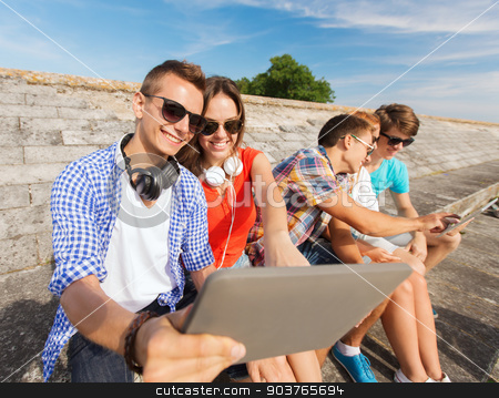 group of smiling friends with tablet pc outdoors stock photo, friendship, leisure, summer and people concept - group of smiling friends with tablet pc computers sitting outdoors by Syda Productions