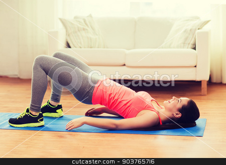 smiling girl doing exercise for legs and buttocks stock photo, fitness, home and diet concept - smiling teenage girl doing exercise for legs and buttocks on floor at home by Syda Productions