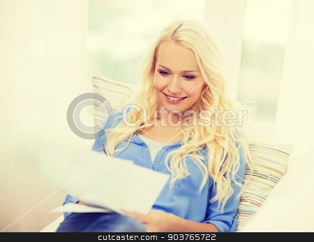 smiling young woman with papers at home stock photo, tax, finances, home and happiness concept - smiling young woman with papers at home by Syda Productions