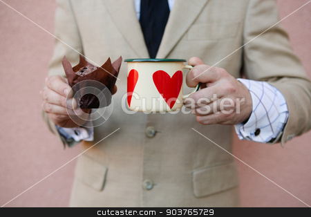 man holding hot cup of coffee stock photo, woman holding hot cup of coffee with heart by Andriy