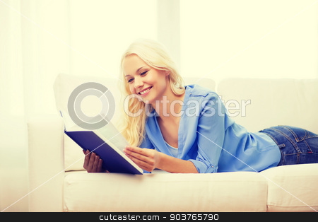 smiling woman reading book and lying on couch stock photo, leasure and home concept - smiling woman reading book and lying on couch at home by Syda Productions