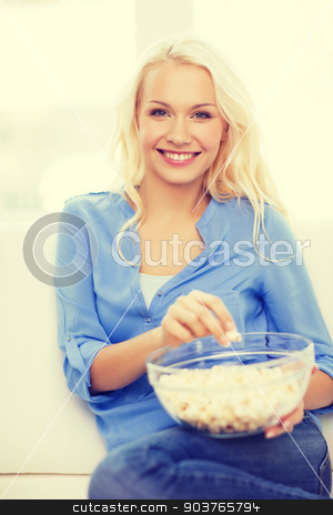 young girl with popcorn ready to watch movie stock photo, food, happiness and people concept - smiling young girl with popcorn ready to watch movie at home by Syda Productions