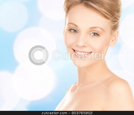 beautiful young woman face stock photo, beauty, people and health concept - beautiful young woman face over blue lights background by Syda Productions