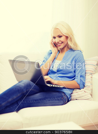 smiling woman with smartphone and laptop at home stock photo, home, technology and internet concept - smiling woman with smartphone and laptop computer sitting on couch at home by Syda Productions