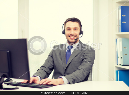 helpline operator with headphones and computer stock photo, business, communication, technology and call center concept - friendly male helpline operator with headphones and computer at call center by Syda Productions