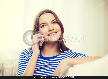smiling teenage girl with smartphone at home stock photo, home, technology and communication concept - smiling teenage girl with smartphone sitting on couch at home by Syda Productions