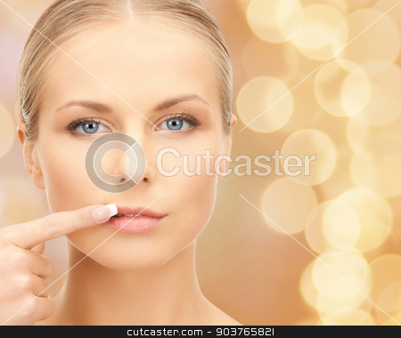 beautiful young woman pointing finger to her lips stock photo, beauty, people and health concept - beautiful young woman pointing finger to her lips over beige lights background by Syda Productions