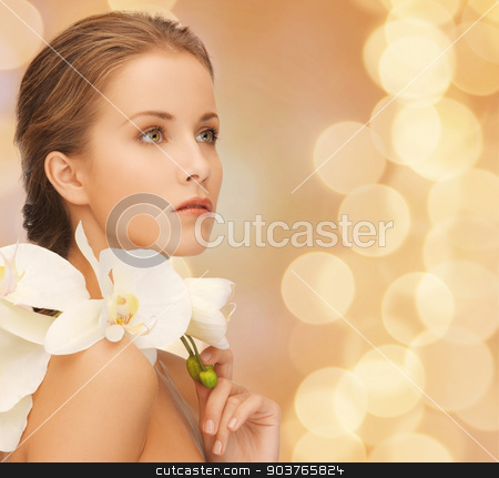beautiful young woman with orchid flowers stock photo, beauty, people and health concept - beautiful young woman with orchid flowers and bare shoulders over beige lights background by Syda Productions