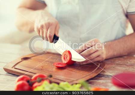 male hand cutting tomato on board with knife stock photo, cooking and home concept - close up of male hand cutting tomato on cutting board with sharp knife by Syda Productions