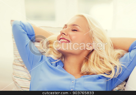 smiling young woman lying on sofa at home stock photo, home and happiness concept - smiling young woman lying on sofa at home by Syda Productions