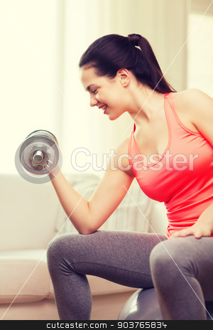 smiling girl exercising with dumbbells stock photo, fitness, home and diet concept - smiling girl exercising with fitness ball and dumbbells at home by Syda Productions