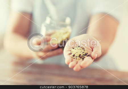 male with white and wild black rice on palm stock photo, cooking and home concept - close up of male hand with pile of mixture of white and wild black rice by Syda Productions