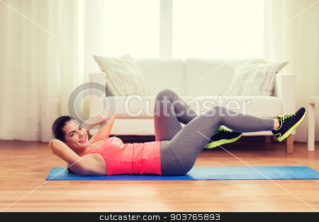smiling girl doing exercise on floor at home stock photo, fitness, home and diet concept - smiling teenage girl doing exercise on floor at home by Syda Productions