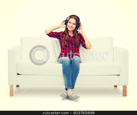 teenage girl sitting on sofa with headphones stock photo, home, leisure and happiness concept - smiling teenage girl sitting on sofa with headphones by Syda Productions