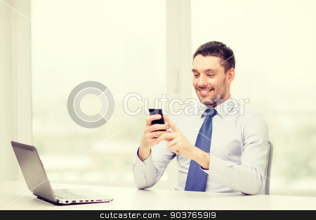 businessman with laptop and smartphone at office stock photo, business, office and technology concept - smiling businessman with laptop computer and smartphone at office by Syda Productions