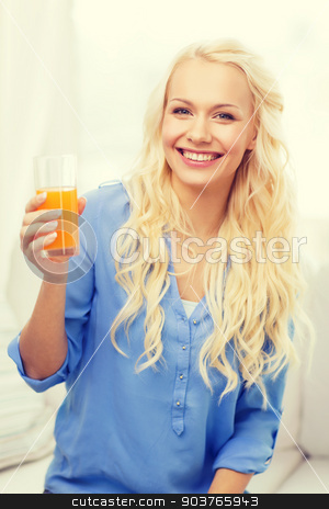 smiling woman with glass of orange juice at home stock photo, healthcare, food, home and happiness concept - smiling young woman with glass of juice having breakfast at home by Syda Productions