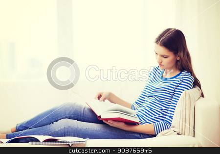 calm teenage girl reading book on couch stock photo, leasure and home concept - calm teenage girl woman reading book and sitting on couch at home by Syda Productions