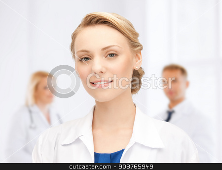 smiling young female doctor in hospital stock photo, medicine, people, profession and teamwork concept - smiling young female doctor over group of medics in hospital by Syda Productions