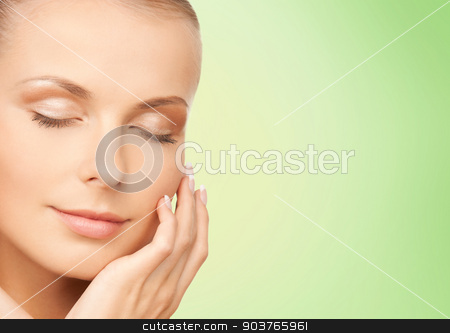 beautiful young woman touching her face stock photo, beauty, people and health concept - beautiful young woman touching her face over green background by Syda Productions