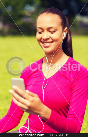 smiling african american woman with smartphone stock photo, fitness, park, technology and sport concept - smiling african american woman with smartphone and earphones sitting on mat outdoors by Syda Productions