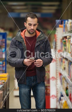 Young Man Typing On Mobile Phone At Supermarket stock photo, Smiling Young Man Using Mobile Phone While Shopping In Shopping Store by Jasminko Ibrakovic