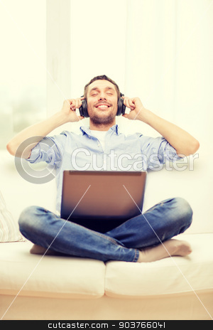 smiling man with laptop and headphones at home stock photo, technology, home, music and lifestyle concept - smiling man with laptop and headphones at home by Syda Productions