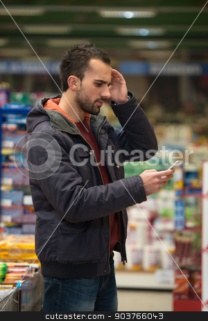 Man Looking Confused At Mobile Phone In Supermarket stock photo, Smiling Young Man Using Mobile Phone While Shopping In Shopping Store by Jasminko Ibrakovic