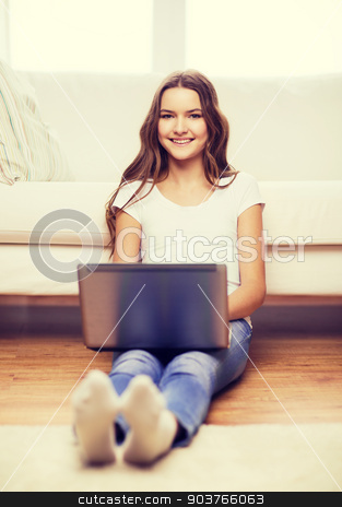 smiling teenage girl with laptop computer at home stock photo, home, technology and internet concept - smiling teenage girl sitting on the floor with laptop computer at home by Syda Productions