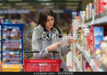 Woman Reading Her Shopping List In The Supermarket stock photo, Beautiful Young Woman Reading Her Shopping List In Produce Department Of A Grocery Store - Supermarket - Shallow Deep Of Field by Jasminko Ibrakovic