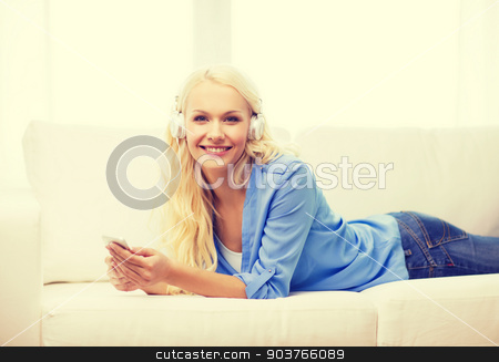 woman with smartphone and headphones at home stock photo, home, technology and internet concept - smiling woman with smartphone and headphones lying on couch at home by Syda Productions