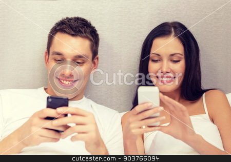 smiling couple in bed with smartphones stock photo, hotel, travel, relationships, technology, intermet and happiness concept - smiling couple in bed with smartphones by Syda Productions