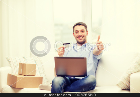 man with laptop, credit card and cardboard boxes stock photo, technology, home and lifestyle concept - smiling man with laptop, credit card and cardboard boxes at home showing thumbs up by Syda Productions