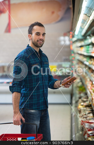 Young Man Shopping In The Supermarket stock photo, Handsome Young Man Shopping For Fruits And Vegetables In Produce Department Of A Grocery Store - Supermarket - Shallow Deep Of Field by Jasminko Ibrakovic