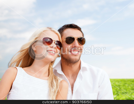happy couple in shades over natural background stock photo, summer holidays, people and dating concept - happy couple in shades over blue sky and grass background by Syda Productions