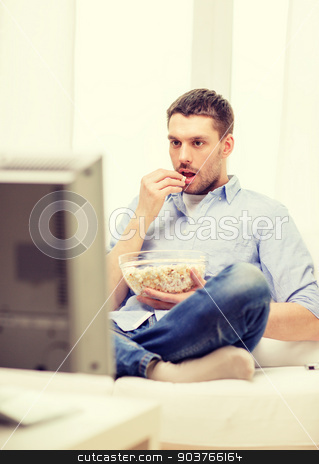 smiling man watching sports at home stock photo, sports, food, happiness and people concept - smiling man with popcorn watching sports on tv and supporting team at home by Syda Productions