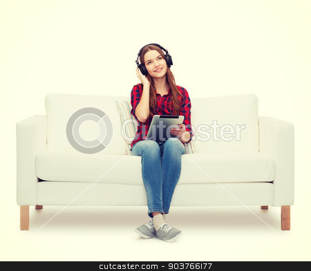 girl sitting on sofa with headphones and tablet pc stock photo, home, leisure, technology and happiness concept - smiling teenage girl sitting on sofa with headphones and tablet pc computer by Syda Productions