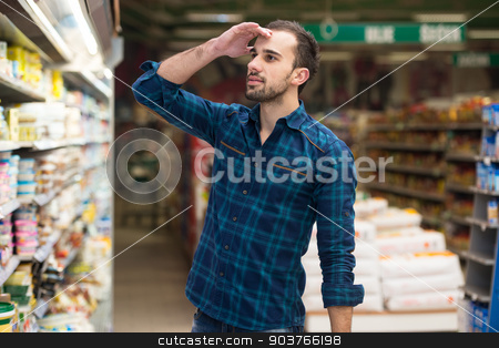 Confused Man Shopping At The Supermarket stock photo, Handsome Young Man Shopping For Fruits And Vegetables In Produce Department Of A Grocery Store - Supermarket - Shallow Deep Of Field by Jasminko Ibrakovic