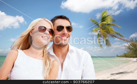 couple in shades over tropical beach background stock photo, summer holidays, travel, tourism, people and dating concept - happy couple in shades over tropical beach background by Syda Productions