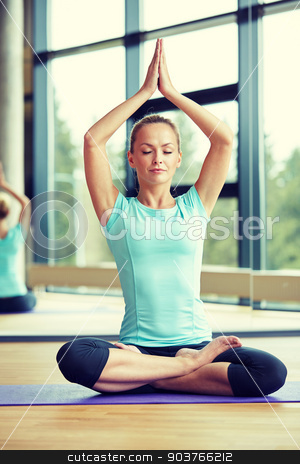 happy woman meditating in lotus pose on mat stock photo, fitness, sport, yoga and people concept - happy woman with closed eyes meditating in lotus pose on mat in gym by Syda Productions