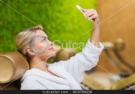 beautiful young woman with smartphone at spa stock photo, people, beauty, lifestyle, technology and relaxation concept - beautiful young woman in white bath robe taking selfie with smartphone at spa by Syda Productions