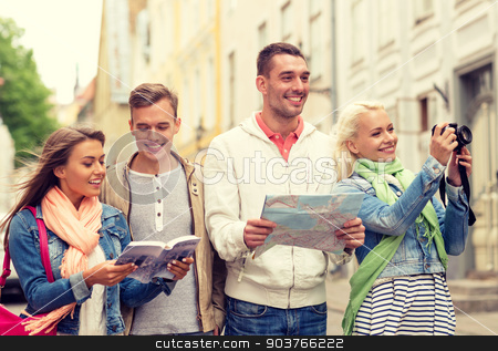group of friends with city guide, map and camera stock photo, travel, vacation, technology and friendship concept - group of smiling friends with city guide, photocamera and map exploring city by Syda Productions
