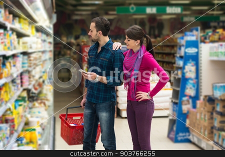 Couple Shopping At The Supermarket stock photo, Beautiful Young Couple Shopping For Fruits And Vegetables In Produce Department Of A Grocery Store - Supermarket - Shallow Deep Of Field by Jasminko Ibrakovic