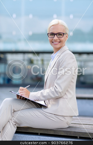 young smiling businesswoman with notepad outdoors stock photo, business, people and education concept - young smiling businesswoman in glasses with notepad over office building by Syda Productions
